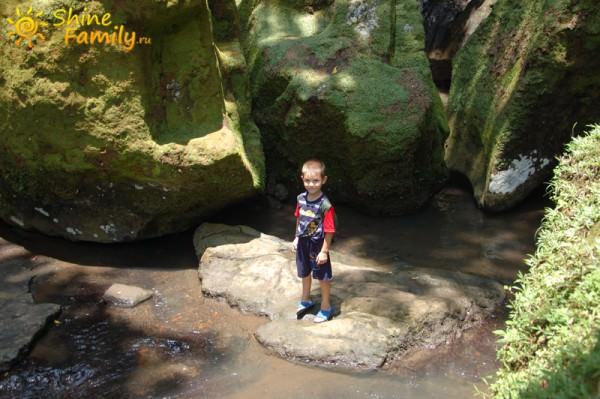 Никита прыгает по речным камням